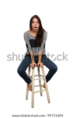 A lovely young brunette in casual wardrobe, with a surprised or shocked facial expression, sits on a barstool, isolated on a white background with generous copyspace.