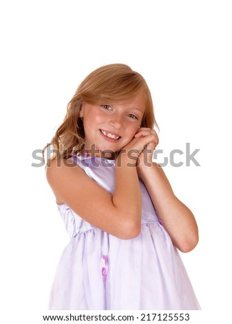 A lovely young girl in a pink dress with her hands on her face standing isolated for white background.