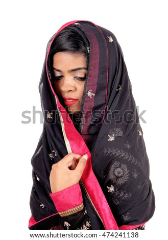 A lovely young Indian woman covered in a black veil, looking down,