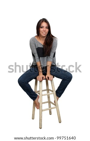 A lovely young smiling brunette in casual wardrobe sits on a barstool, isolated on a white background with generous copyspace.