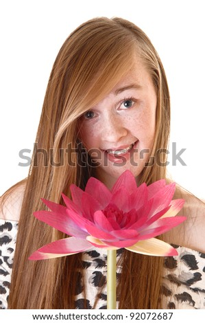 A lovely young teenage girl in a portrait picture with a pink water lily, smiling into the camera, with long hair for white background. - stock photo