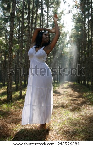 A lovely young woman outdoors, wearing a white nightgown, backlit by the sun. - stock photo