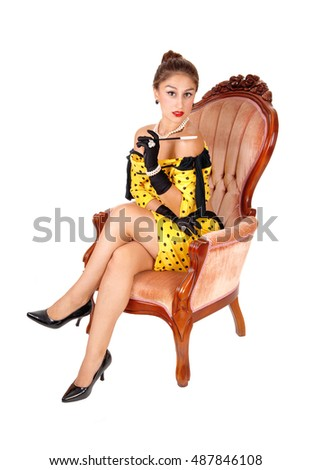 A lovely young woman sitting in a yellow dress in a pink armchair holding