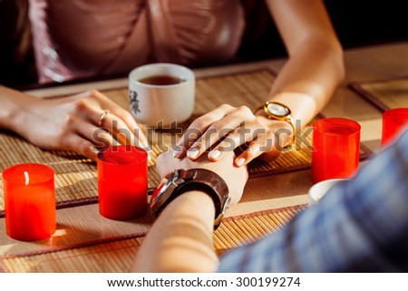 A loving couple is passionately holding hands at a dating. - stock photo