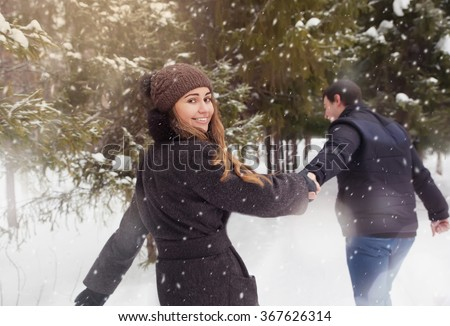A loving couple walking in winter park. It's snowing, winter. - stock photo