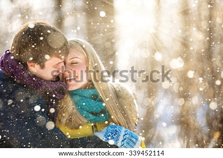 A loving couple walking in winter park with pine trees. Forest in snow. The snowfall, snowflakes shine in the sun. Frosty cold. People dressed in colorful jackets and scarves. Copy space. - stock photo