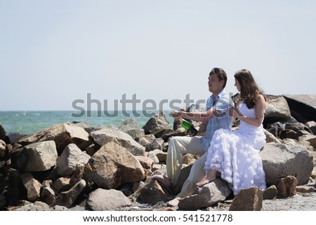 A loving couple walks on the sea. Couple in the summer at sea. Sea Wedding. Bride and groom fooling around. The bride and groom open champagne with splashes.