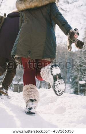 A loving happy young couple emotionally runs in the winter woods. View back - stock photo
