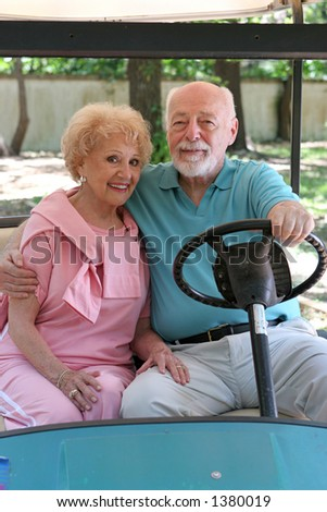A loving senior couple in a golf cart.