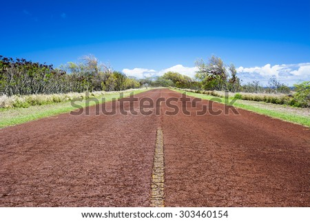A low angle perspective of an asphalt country road covered in red desert dirt. - stock photo