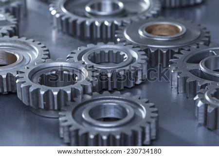 A low angle photograph with a shallow depth of field featuring multiple metal gears linked together - stock photo