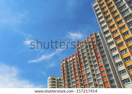 A low angle shot of a new colorful high rise apartment against the sky. - stock photo
