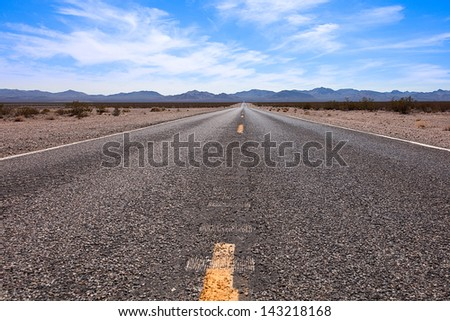 A low angle shot of an American highway in the Nevada desert. - stock photo