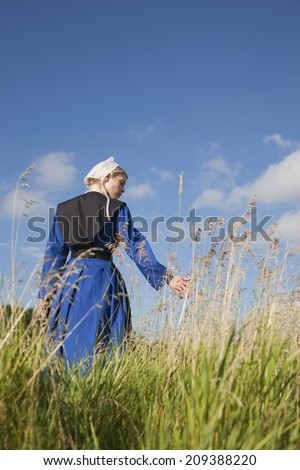 A low angle view of an Amish girl walking in a field touching the grass - stock photo