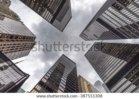 A low angle view of skyscrapers on an grey overcast day. - stock photo