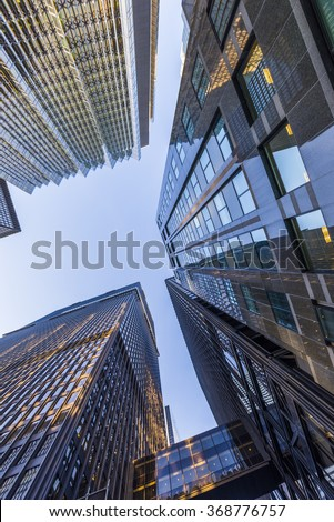 A low angle view of skyscrapers with dappled sunlight against a blue sky.