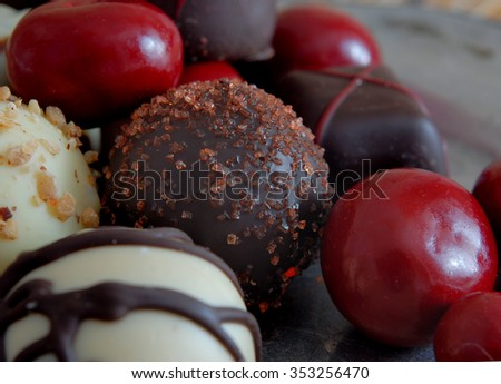 A low key, close-up view of a variety of bite sized chocolates in different shapes. Some are covered with red candy coating. Some are decorated. Dark chocolate and white chocolate included.