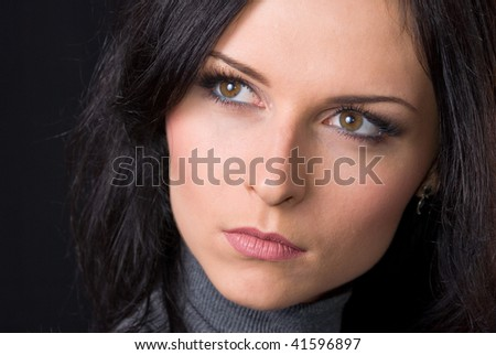 A low key portrait of a gorgeous brunette woman in a grey turtleneck isolated on black background
