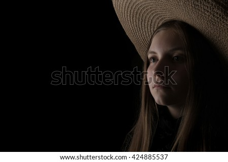 A low key portrait of a teenage girl in a serious mood. With only one light source, a big hat, and soft colors, this is a dramatic photo for many ideas and concepts. Horizontal with copy space.