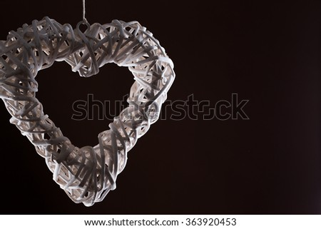 A low lit white hanging heart against a dark background
