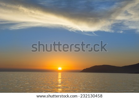 A low, orange sunset and blue sky reflects off the surface of the ocean, creating an ideal memory of nature.  - stock photo