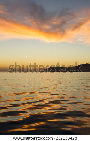 A low, orange sunset reflects off the surface of the ocean, creating a beautiful wavy, natural pattern and lights up the sky - stock photo