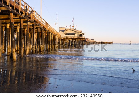 A low, setting sun casts a deep orange light on the pilings of the Santa Barbara pier, also know as Stearns Wharf. - stock photo