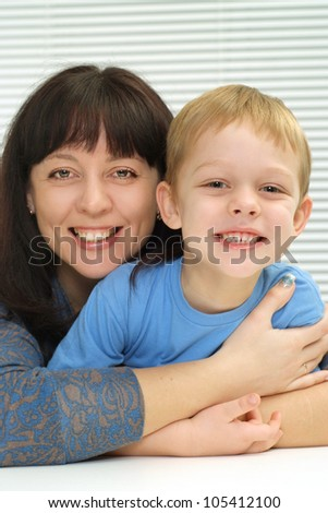 A luck Caucasian mother and son a light background - stock photo