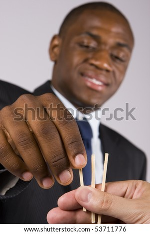 A lucky business man choosing a straw - Focus on the hands - stock photo