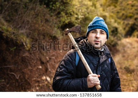 a lumberjack or a psychopath holding a rusty hatchet - stock photo