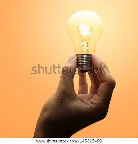 A luminescent light bulb hold by a human hand. Warm light. - stock photo