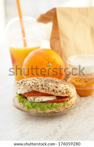 A lunch consisting of a sandwich and orange juice - stock photo