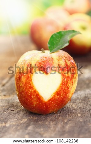 A luscious ripe red apple standing on a wooden table with a neat heart shape incised in the skin conceptual of I love apples - stock photo