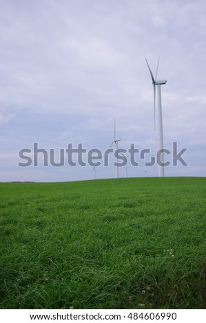 A lush grassy field with wind turbines against a cloudy sky. See portfolio for a similar photo in landscape orientation.