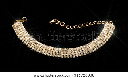 A luxurious gold diamond bracelet against a black background - stock photo