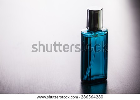 a luxurious perfume bottle on a wooden table with copy space - stock photo