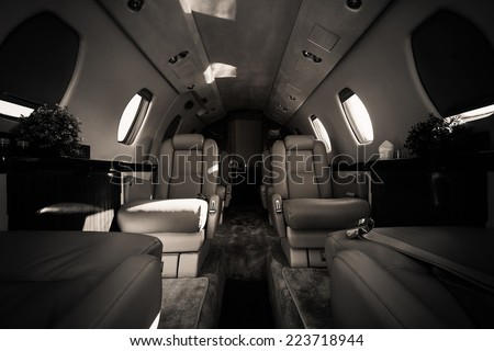 a luxury aircraft interior, leather seats, poor light - stock photo