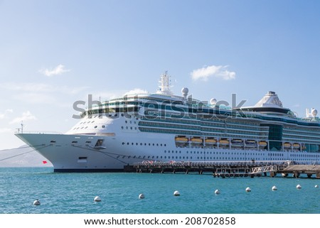 A luxury cruise ship at a pier with passengers disembarking - stock photo