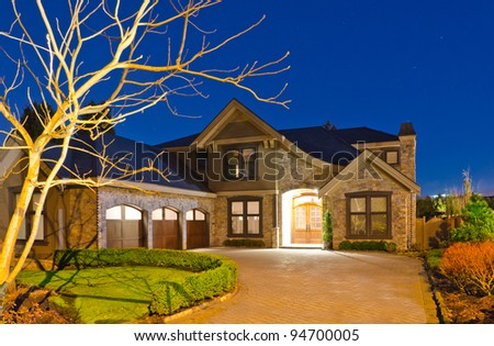 A luxury house with big driveway  and three garage doors in suburbs at dusk in Vancouver, Canada