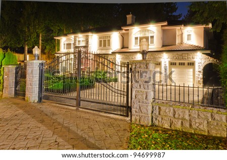 A luxury house with the gates in suburbs at dusk in Vancouver, Canada - stock photo