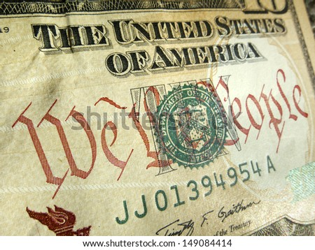"""A macro close up photo emphasizing the inscription """"We The People"""" printed on the back of a United States ten dollar bill with selective focus on the words 'We The People'. - stock photo"""