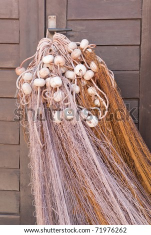 a macro of a fishing net hanging in the sun to dry - stock photo