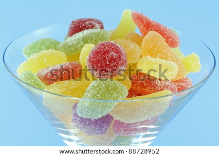 A macro photo of a glass full of assortment of colorful fruity chewy gummy, sweet and sour candy on bright blue background