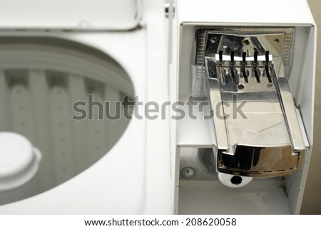 A macro shot of a coin operated washing machine to keep your clothes clean. - stock photo