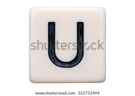 A macro shot of a game tile with the letter U on it on a white background.