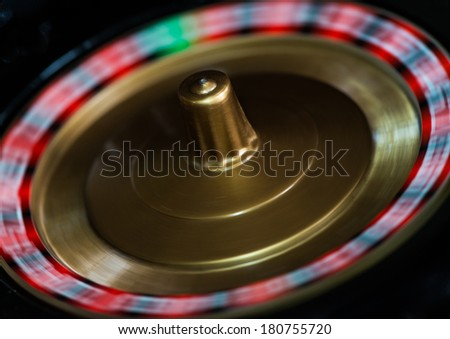 A macro shot of a spinning toy roulette wheel. - stock photo