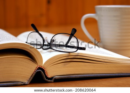 A macro shot of an open book with reading glasses and a cup of coffee. - stock photo