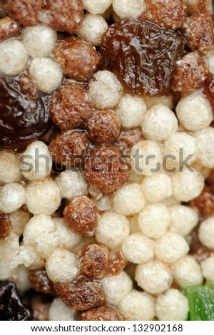 A macro shot of cereal bar with puffed rice, chocolate puffed rice, raisins, and candied fruits - stock photo