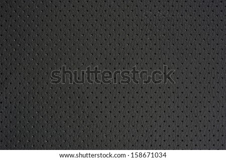 A macro shot of dark gray perforated artificial leather background texture - stock photo