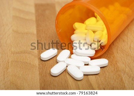 A macro shot of some acetaminophen spilling from it's pill bottle. - stock photo